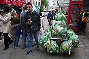 Street cleaner with a fully laden rubbish cart with bags of waste in London, England, United Kingdom. Rubbish recycling bags collection of recyclable waste in the city.