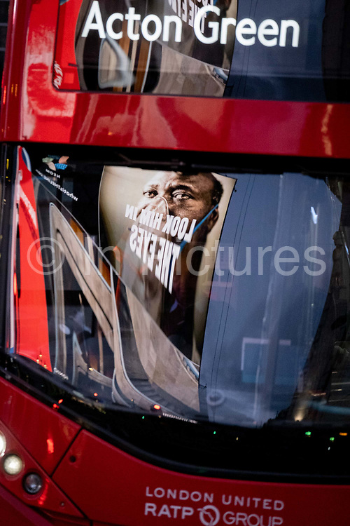 Seen reflected in the windscreen of a passing bus, a government NHS National Heath Service ad displays the face of a Covid patient, urging Londoners to stay at home and not to take risks or bend the rules during the third lockdown of the Coronavirus pandemic, at Piccadilly Circus in the capitals West End, on 5th February 2021, in London, England.