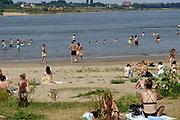 Nederland, nijmegen, 12-8-2020 Vooral jonge mensen zoeken verkoeling aan de oevers van de waal op deze tropisch warme zomerdag . Het is eigenlijk verboden in de rivier te zwemmen vanwege de stroming en het drukke scheepvaartverkeer . Deze strandje liggen tussen de kribben in de Stadswaard . Helaas is er ook nogal wat overlast, met name in de avond als er gefeest en gedronken wordt . Ook wordt er veel afval, vuil achtergelaten. Foto: ANP/ Hollandse Hoogte/ Flip Franssen