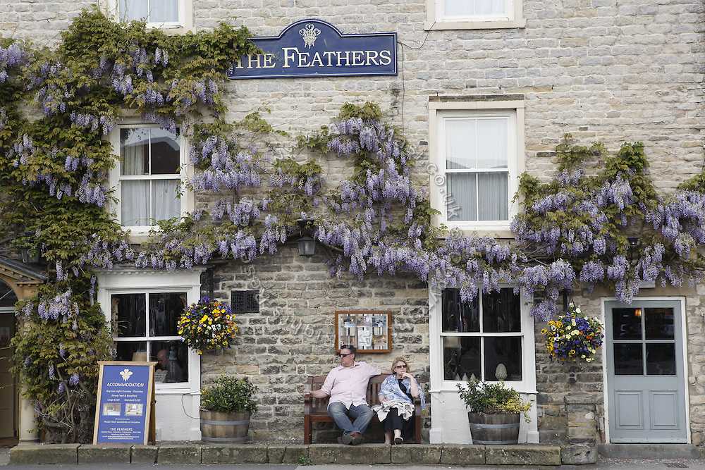 A couple is sitting on a bench at The Feathers pub in Helmsley, Yorkshire, England, United Kingdom.