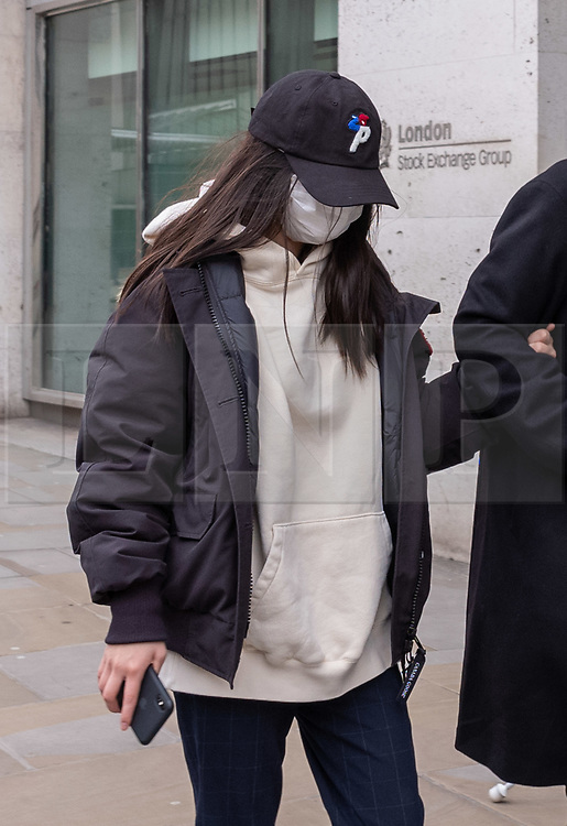 © Licensed to London News Pictures. 09/03/2020. London, UK. A women with a protective mask walks past the London Stock Exchange today as markets around the world plunge as fears over the Coronavirus disease continues. Photo credit: Alex Lentati/LNP