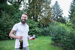 Young man holding red wine with glasses in garden, Bavaria, Germany