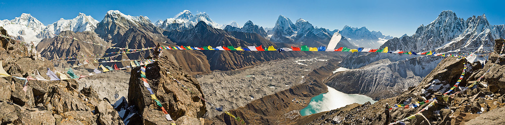 """Prayer flags fly from the trekkers' peak of Gokyo Ri (17,575 feet / 5357 meters elevation). See Mount Everest (center left), adjacent Lhotse, and the distant pyramid of Makalu. The largest glacier in Nepal, Ngozumpa Glacier, flows down the valley floor covered in gray rocks. Its lateral moraine dams several lakes. To the left of Third Gokyo Lake is Gokyo village (15,583 feet / 4750 meters), a small cluster of teahouses for trekkers and climbers. Sagarmatha National Park was created in 1976 and honored as a UNESCO World Heritage Site in 1979. Panorama stitched from 5 images. Published in """"Light Travel: Photography on the Go"""" book by Tom Dempsey 2009, 2010."""