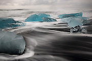 Blue icebergs in the surf at Jökulsárlón beach in South-East Iceland