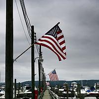Verenigde Staten.Rockland.Piermont.9 augustus 2005.<br /> Bewoners van het Havenplaatsje Piermont aan de Hudson rivier zo'n 40 km buiten New York.<br /> Vele bewoners van Piermont en van New York hebben een boot in de haven liggen.Piermont is het 1e dorpje aan de Hudson ten Westen van New York.<br /> Amerikaanse vlag.haven.Boten.Bewolking.Kade.<br /> Archives 2005, in the marina of Piermont, New York USA.