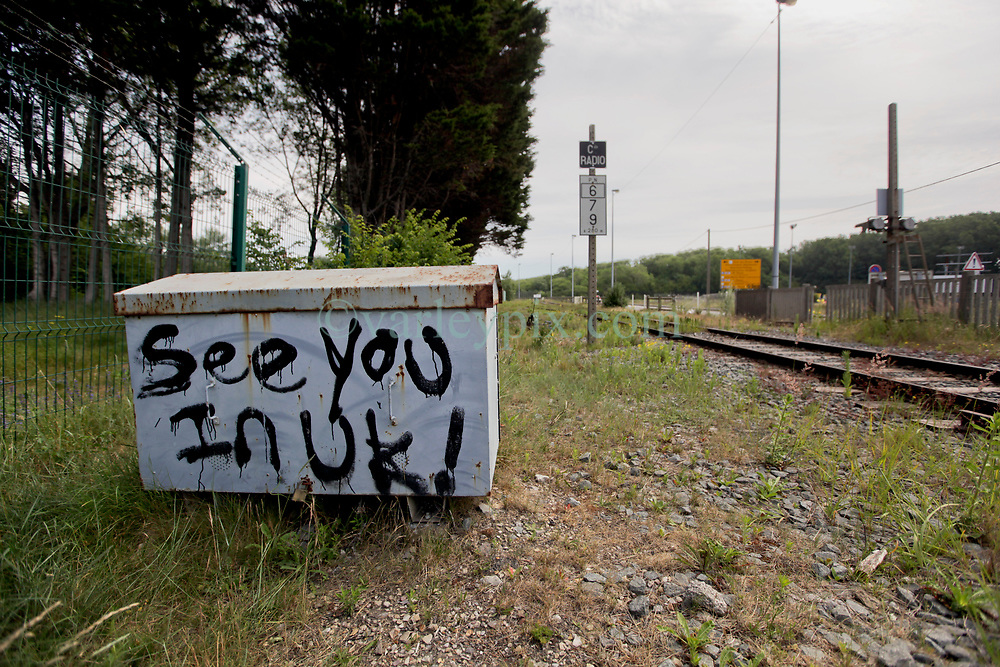 26 June 2020. Zone des Dunes, refugee camp, Calais, France.<br /> 'See you in UK!' Graffiti painted on a train signalling control box close to Zone des Dunes refugee camp in Calais. Several tented refugee camps have cropped up to replace the notorious 'Jungle' camp which was dismantled by French authorities in October and November 2016. Migrants assembling in the Zone are making often desperate attempts to cross the English Channel (La Manche) by boat, surf board and even inflatable paddling pools as numbers seeking asylum in the UK continue to rise. <br /> Photo©; Charlie Varley/varleypix.com
