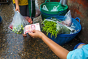 """26 SEPTEMBER 2012 - BANGKOK, THAILAND:  A vendor hands a 100 Baht note change back to a customer in Khlong Toey Market in Bangkok. Khlong Toey (also called Khlong Toei) Market is one of the largest """"wet markets"""" in Thailand. The market is located in the midst of one of Bangkok's largest slum areas and close to the city's original deep water port. Thousands of people live in the neighboring slum area. Thousands more shop in the sprawling market for fresh fruits and vegetables as well meat, fish and poultry.    PHOTO BY JACK KURTZ"""