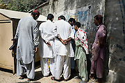 Celebrated young pakistani artist Asim Butt on a journey of political graffiti through Pakistan during the summer of 2009..Onlookers in the town of lakana come to view the piece 'paint it black' which refers to benazir Bhutto's death.