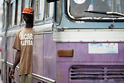 A man stands in the door of a bus as it drives through traffic in central Accra, Ghana on Tuesday June 16, 2009.