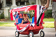 A young child dressed in patriotic costume is pulled along in a wagon during the annual I'On Community Independence Day Parade on July 4, 2012 in Mt Pleasant, South Carolina.