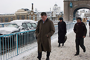 Heavy overnight snowfall covers London in a thick blanket of fine snow. The heaviest snowfall in decades. Commuters walk across Tower Bridge. Almost all public transport has been cancelled.