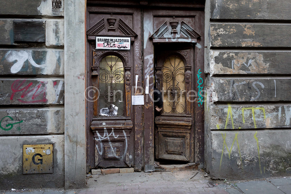 A hand in an open doorway of a property in the heart of the Jewish Kazimierz district of Krakow - the location of Nazi Holocaust evacuations during WW2 and where Steven Spielberg filmed scenes for his film Schindlers List, on 23rd September 2019, in Krakow, Malopolska, Poland. The Jewish community were systematically removed from Kazimierz and taken to what became the Krakow Ghetto across the Vistula river in the Podgorze district where Oskar Schindlers factory was located and where he went on to save 1,100 Jews from concentration camps all over Poland and Germany. Before the war, 64,000 Jews lived in Krakow but after liberation, only 3-4,000 survived.