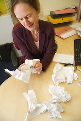 Stressed office worker crumpling up paper.