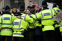 "© Licensed to London News Pictures . 05/01/2019. Manchester, UK. Protesters and police clash as police try to keep tram lines clear on Mosley Street when protesters hold an impromptu march from St Peter's Square to Piccadilly Gardens . A Yellow Vest demonstration takes place in St Peter's Square in central Manchester . The protest was organised via YouTube account "" Tommy Robinson News "" and was called in the wake of stabbings at Manchester Victoria Train Station on New Year's Eve . Protesters chanted in favour of Brexit , against police and press and carried pro-Trump and EDL clothing and placards . Photo credit : Joel Goodman/LNP"