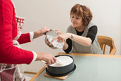 Senior woman nibbling meringue with finger in kitchen, Munich, Bavaria, Germany
