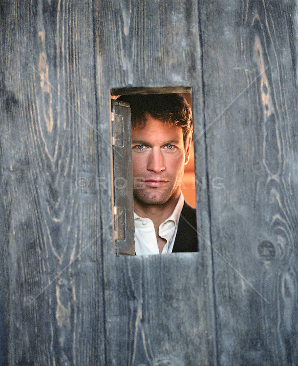Handsome man looking out a small window on a wooden door