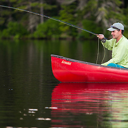 A man fly-fishing for brook trout from a canoe on Lang Pond in Maine's Northern Forest. Cold Stream watershed, Parlin Pond Township.
