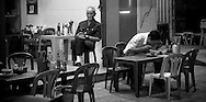 In a street restaurant a a man is eating a vietnamese soup (pho) while an other man is sleeping on a chair. Nha Trang, Vietnam, Asia