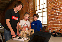 Ryan Dee, a junior at Laconia High School, explains to Sam Kelley and Brendan Dee the strength of his wooden bridge design project built in Manufacturing and Engineering class at Huot Technical Center during Makers Night at the Belknap Mill Thursday evening.    (Karen Bobotas/for the Laconia Daily Sun)