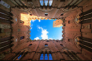 Torre del Mangia towering above of the Palazzo Pubblico<br /> <br /> The Torre del Mangia is a tower in Siena, in the Tuscany region of Italy. Built in 1325-1344, it is located in the Piazza del Campo, Siena's premier square, adjacent to the Palazzo Pubblico (Town Hall). When built it was one of the tallest secular towers in mediaeval Italy.