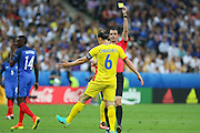Referee Viktor Kassai shows a yellow card to Romania Defender Vlad Chiriches during the Group A Euro 2016 match between France and Romania at the Stade de France, Saint-Denis, Paris, France on 10 June 2016. Photo by Phil Duncan.