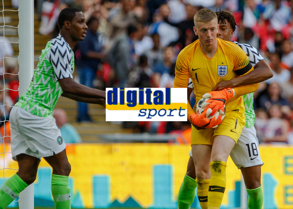 Football - 2018 International Friendly (pre-World Cup warm-up) - England vs. Nigeria<br /> <br /> Alex Iwobi (Nigeria) tries to wrestle the ball free from Jordan Pickford (England) after he scores to reduce his teams deficit at Wembley Stadium.<br /> <br /> COLORSPORT/DANIEL BEARHAM
