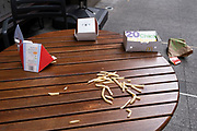 Discarded chips (French Fries) and McDonalds packaging lie on the ground and on a cafe table in central London, on 26th September 2021, in London, England.