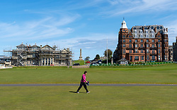 St Andrews, Scotland, UK. 4 May 2020.  The famous Old Course at St Andrews is closed due to the coronavirus lockdown. Locals are making the most of the closed golf course by using it as a park for they daily exercise. Woman walks across first and eighteenth fairways.  Iain Masterton/Alamy Live News