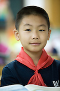 A Chinese school boy in class in Beijing, wearing a red scarf, indicating he is a member of the Young Pioneers.The Young Pioneers of China is run by the Communist Youth League, an organization of older youth that comes under the Communist Party of China. The YP of China is similar to Pioneer Movements that exist or existed in many Communist countries around the world.