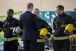 The Duke of Cambridge speaks to emergency services personnel as she arrives to meet members of the community affected by the fire at Grenfell Tower in west London during a visit to the Westway Sports Centre which is providing temporary shelter for those who have been made homeless in the disaster.