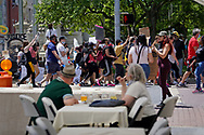 """A couple eats at at the outdoor seating of a restaurant as hundreds of protesters march around them June 7, 2020, during a Black Lives Matter """"Circle of Peace"""" protest at Centre Square in Easton, Pennsylvania. (Photo by Matt Smith)"""
