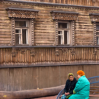 Russian women chat on a bench below an ornately carved log building in the northern port city of Arkhangel'sk.