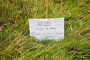 Sign saying adders in the meadow please do not walk across grass field, UK