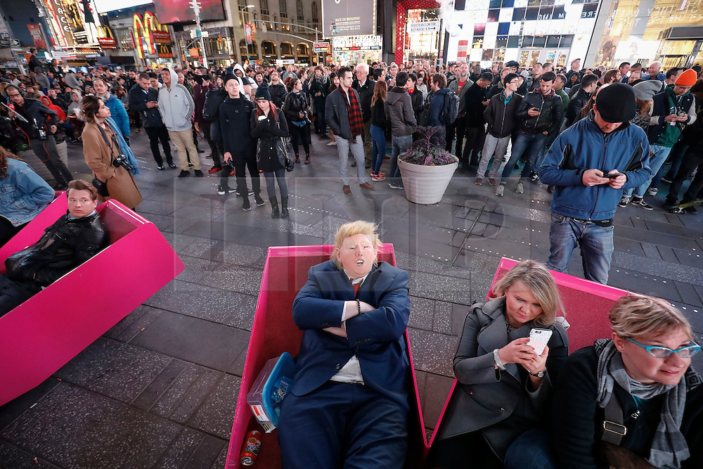 © Licensed to London News Pictures. 09/11/2016. New York City, USA. A man dressed as Donald Trump watches the election coverage unfold on large screens in Times Square, New York City, on Wednesday, 9 November. Photo credit: Tolga Akmen/LNP