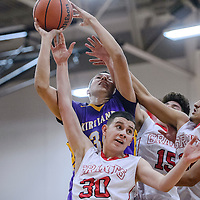 Kirtland Central Bronco Nathan Enoa (34) fights a rebound away from Grants Pirates Kevin Sierra (30) and Adrian Sanchez (32) Monday at Grants High School.