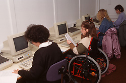 Group of women including woman with disability; who is wheelchair user; using computers in office,