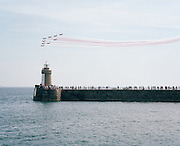 The Red Arrows, Britain's RAF aerobatic team, perform their public display over a harbour wall seaside crowd landscape.