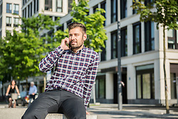 Young man talking on the mobile phone in city, Munich, Bavaria, Germany