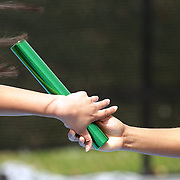 A baton change during relay competition at the 2013 NYC Mayor's Cup Outdoor Track and Field Championships at Icahn Stadium, Randall's Island, New York USA.13th April 2013 Photo Tim Clayton