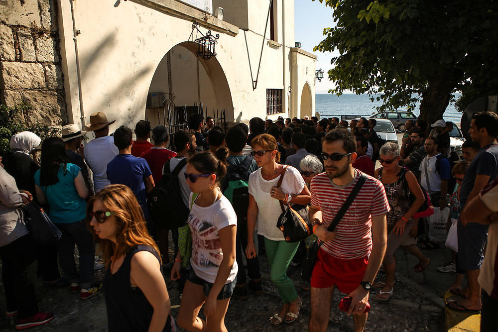 Tourists walk past dozens of migrants and refugees waiting outside a police station to be registered for their documents to leave the Greek island of Kos on July 5, 2015.