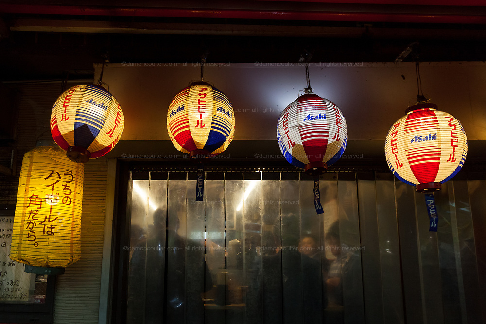 Paper lanterns outside a small bar in Ueno where iJapanese office workers, or salarymen, are enjoying  after work drinks. Tokyo, Japan. Monday April 15th 2019