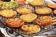 fried green tomatoes,on a rack over newspaperon a wooden table