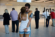 """Amid the hectic arrivals concourse of Heathrow airport's Terminal 5, a young couple kiss and hold on to each other after a few weeks separation when the girl took a family holiday away from her boyfriend who needed to work here in London. They have clearly missed each other after such a short break from each other but are otherwise oblivious to the crowds that surround them in this busy international airport. The boy holds the girl's bottom in a display of sexuality that is frowned upon in other cultures where open sexual behaviour is taboo. From writer Alain de Botton's book project """"A Week at the Airport: A Heathrow Diary"""" (2009)."""