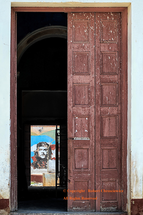 Omnipresent Che: Through multiple doors of a building being renovated, the omnipresent Che Guevara is seen on the walls of an inner courtyard, Trinidad Cuba.