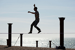 © Licensed to London News Pictures. 29/03/2014. Brighton, UK . A man practices the tightrope on the seafront. People enjoy the sunny weather in Brighton today 29th March 2014. The warm weather is forecast to remain into next week. Photo credit : Stephen Simpson/LNP