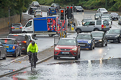 ©Licensed to London News Pictures 21/10/2020  <br /> Aylesford, UK. A cyclists in flood water. Wet driving conditions and a flooded A20 London road at Aylesford in Kent near Maidstone. The Met office has issued a severe weather warning for the UK as storm Barbara comes in from Spain bringing winds and torrential rain. Photo credit:Grant Falvey/LNP