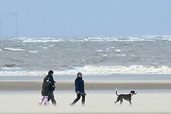 © Licensed to London News Pictures. 27/12/2013. New Brighton, UK People play and walk in the high winds and the windswept sands at New Birghton on Wirral today 27 December 2013 . Photo credit : Stephen Simpson/LNP