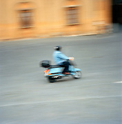Moped rides through the Piazza Del Campo, Siena, Tuscany, Italy