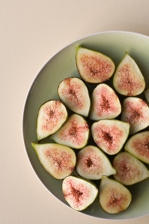 Birds eye view of sliced juicy red centred fresh figs on a green plate.