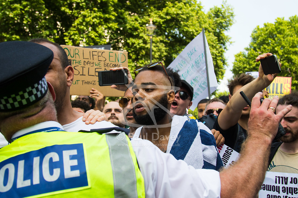London, June 21st 2017. Protesters march through London from Sheherd's Bush Green in what the organisers call 'A Day Of Rage' in the wake of the Grenfell Tower fire disaster. The march is organised by the Movement for Justice By Any Means Necessary and coincides with the Queen's Speech at Parliament, the destination. PICTURED: A protester argues with a police officer outside the gates of Downing Street.